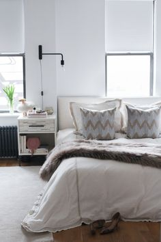 Francesca Falzone's NYC Apartment Tour  #theeverygirl // wall sconces // bedroom // neutral bedding // windows behind bed