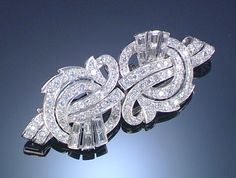 DIAMOND DOUBLE CLIP BROOCH, 1950S Designed as stylised loose ribbons set with circular-, single-cut and baguette diamonds.