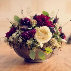 Figs, seeded eucalyptus, Queen Anne's lace, scabiosa flowers, scabiosa pods, nigella pods, dahlias, and garden roses.