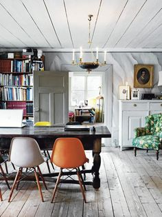 Mixing vintage and modern. And oh my god the green and orange chairs on those floor boards.