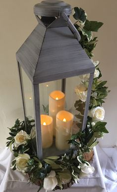 Lantern centrepiece with garland trim and LED candles. #piecesandposies