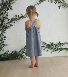 long breezy summer dress with big pockets and gathering across chest. straps can be used as a halter top or crossed and buttoned with adjustable buttonholes.12m, 18m, 2/3, 4/5, 6/7, 8/9100% cottonmade in usa