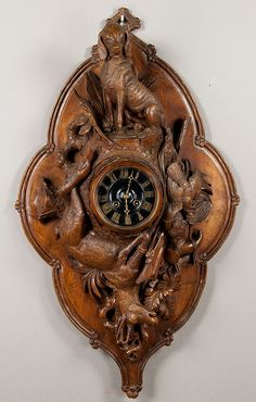 wooden carved wall clock with dog, chamois and hunting accessories.