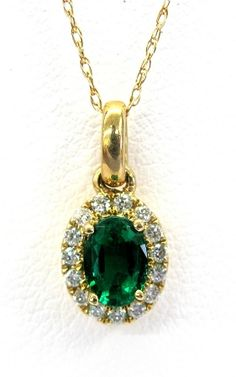 Ladies 14kt yellow gold gemstone and diamond pendant. Mounted in pendant is a oval cut emerald and 15 brilliant round cut diamonds weighing approximately a total of approximately .13ct. Pendant comes with an 18 inch yellow gold chain.