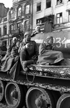 Injured Soviet soldiers rest on a Soviet T-34 85 medium tank during the last throes of the Battle of Berlin