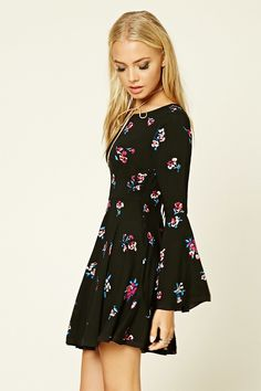 A woven dress featuring an allover floral print, self-tie front, split neckline, long bell sleeves, flared skirt, a short length, and a concealed side zipper.