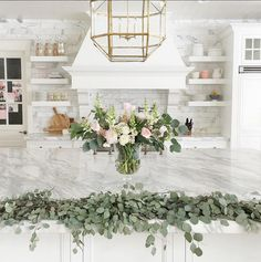 Amazing kitchen styling idea for Easter, featuring gorgeous marble counters and white cabinets decorated with pink peonies and garlands | Asher Associates Architects