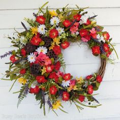 This stunning - extra full wreath is a glorious display of color - rich oranges, canary yellows, lavender plum, crisp whites, moss, avocado, hunter greens and dark chocolate. With careful attention to color, texture, construction and design - this exquisite floral wreath is made from only top quality materials. The wreath features gorgeous premium morning glories, darling double white shasta daisies, mini cattails, latex berries, apple green ferns, velvety moss leaves and interesting lotus…