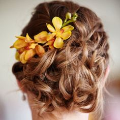 A Casual Curly Updo    Instead of a traditional veil, Laura wanted something unfussy and fresh. Her stylist came up with this curly, pinned-back hairstyle accented with a few yellow Mokara orchids.