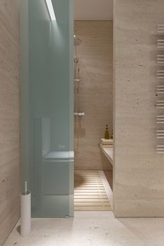 Sleek stone with frosted glass screen in this #bathroom #design