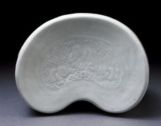 Pillow        Place of origin:        Jingdezhen, China (made)      Date:        1100-1200 (made)      Artist/Maker:        Unknown (production)      Materials and Techniques:        Porcelain, glazed      Credit Line:        Purchased with the assistance of The Art Fund, the Vallentin Bequest, Sir Percival David and the Universities China Committee      Museum number:        C.842-1936      Gallery location:        China, room 44, case 21
