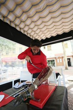 """Probably the greatest and most stylisitic cortador de jamones (Ibérico ham cutter) on the planet, my great friend Florencio """"Flores"""" Sanchidrián prepares to cut a phenomenal Ibérico jamón on the terrace of his Venta El Matadero restaurant in the Legazpi section of Madrid. September 19, 2014. Photo by Gerry Dawes©2014 / gerrydawes@aol.com / Facebook / Twitter / YouTube / Pinterest. Canon 5D Mark III / Canon 17-40mm f/4L USM. +3 boards"""