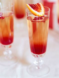 // Pomegranate Spritzer \\  1 cup pomegranate syrup  1 750 ml bottle fruity white wine, such as Mohua Riesling or Bulletin Place Chardonnay (about 3 cups), chilled  1 cup sparkling water, chilled  Pomegranate seeds (optional)  Blood orange wedges (optional)