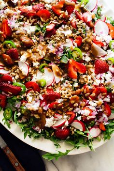 This strawberry salad is colorful and delicious! It's made with arugula, strawberries, goat cheese, sunflower seeds and balsamic vinaigrette. #strawberrysalad #summersalad