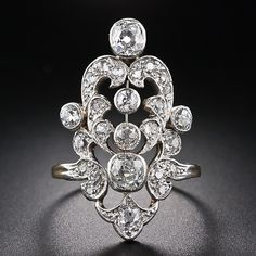 Edwardian Diamond Dinner Ring. An opulent, ornate and sizable (over 1 and 1/8 inch long) late-nineteenth century dinner ring, handcrafted in platinum over 18 karat yellow gold. This regal, gilded age beauty, circa 1890, glistens with 2.00 carats of old mine-cut diamonds.