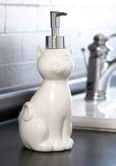 That Suds it Up Soap Dispenser. The white ceramic cat containing your soap is pretty, poised, and perfect for your bathroom renovation. #white #modcloth