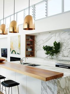 Brass pendant lights, a butcher block bar counter, and gray and white carrara marble kitchen counters, island and backsplash.