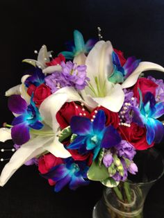 White lilies, red roses, blue bomb dendro orchids with pearl stems