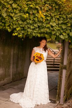 I have another stunner of a photo to share from a wedding at the Arboretum in Guelph, ON!  This photo is of the bride leaning on the wood panel, under a breathing ivy bush that almost touches her head, with her lace over lay dress contrasted with bright sunflower bouquet. It's a beauty of a venue, as it has a perfect blend of urban and nature!