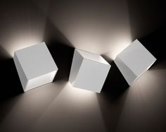 """Pour l'éditeur belge TossB, le designer Alain Monnens signe l'applique murale """"25°"""". Cube tronqué qui semble surgir du mur, elle diffuse deux faisceaux lumineux asymétriques et peut se fixer en toute position pour créer une ..."""