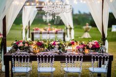 Chandeliers lend timeless elegance to canopied tables filled with ruby red and pastel flowers, an ideal color scheme for the fall months. Via Lin &Jirsa