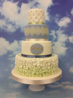 A stunning 4 tier wedding cake in Wedgewood blue featuring ombre ruffles, monogram, edible cake lace and quilting. From The Cake Store, London.