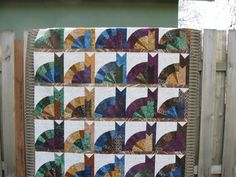 This quilt is calld The Inner Cat.  There are a total of 60 cats large and small each made from a different batik. (Says the source of this photo)