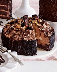 Chocolate Eruption Cheesecake: Chocolate cheesecake holds a rich chocolate mousse and is finished with chocolate curls, sliced almonds, chocolate drizzle, and golden caramel erupting from its center.