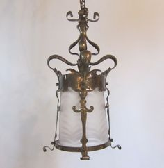English Arts and Crafts lantern in a patinated brass finish complete with the original satin glass shade. www.antiquelightingcompany.com