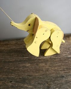 wooden elephant pull toy in the palest yellow. pull on the string and he takes a step forward, then his back legs rock to meet the front.