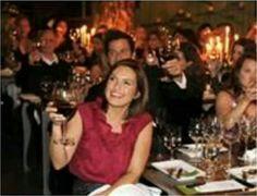 Mariska Hargitay holding her glass of wine  up for a  toast