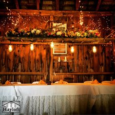 New in 2015, the rustic ladder is lighted by vintage mason jars and hangs over the head table. Playing host to the bridal party and shown here topped with flowers (inquire with our Floral Shoppe about this beautiful service), the ladder is a regular recipient of guests' compliments.
