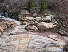 Two patios are connected by a flagstone walkway and large boulders placed in the stream. A firepit is built into the patio area with a natural low stone retaining wall wrapped around the bank. Picture compliments of www.american-stone.com