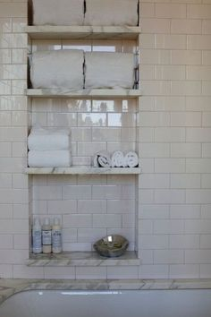 Gorgeous bathroom features drop-in bathtub lined with white marble surround and ivory subway tile shower surround. Shower with niche accented with marble shelves filled with towels and bath accessories. #tilebathtub