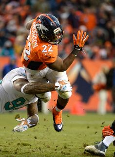 C.J. Anderson (22) of the Denver Broncos is tripped up by Randy Starks (94) of the Miami Dolphins in the third quarter. The Denver Broncos played the Miami Dolphins at Sports Authority Field at Mile High in Denver on November 23, 2014. (Photo by Tim Rasmussen/The Denver Post)-- #ProFootballDenverBroncos