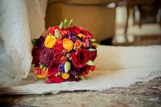 Bridal bouquet with dahlias, ranunculus and hypericum :  wedding bouquet brown dahlias flowers gold hypericum lisianthus orange purple ranunculus red roses spray roses yellow  72 2