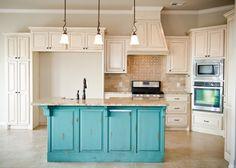 Distressed turquoise island with cream, glazed cabinets, stone mosaic backsplash