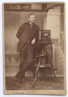 Self-portrait cabinet card of an Illinois photographer, W.W. Griffing, posed with his studio camera.