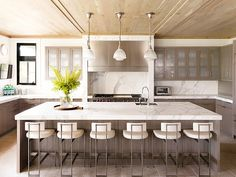 Soft grey cabinets and Carrara marble kitch, massive island, good layout // 8 Stunning Carrara Marble Kitchens to Inspire You via @MyDomaine