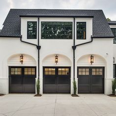 With garage door lighting over each door and plantings in between, these garage doors are absolutely stunning. | Instagram