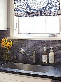 Dark soapstone countertops and dark blue marble tiled backsplash.