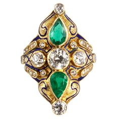 Victorian Pearl Emerald Diamond Gold Ring. The large modified diamond-shaped ring centers 3 bezel-set old European-cut diamonds with 1 pear-shaped bezel-set emerald above and below the center diamond. The four corners are bezel-set with smaller diamonds, the ring accented by 4 rows of five seed pearls, 4 small bezel-set diamonds and blue enamel. Total diamond weight is approximately 2.33 carats, total emerald weight is approximately 1.70 carats.  c 1880
