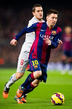 Lionel Messi of FC Barcelona runs with the ball close to Jorge Resurreccion 'Koke' of Club Atletico de Madrid during the La Liga match between FC Barcelona and Club Atletico de Madrid at Camp Nou on January 11, 2015 in Barcelona, Catalonia.