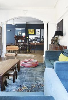 This colourful living area features an archway opening with blue carpet paired with plush velvet vlue sofas. A colourful pouf sits on the floor near the timber coffee table. | A 1914 Durban home is transformed for the 21st century | Inside Out - JUL18 | Design: Koop Design | Photography Elsa Young