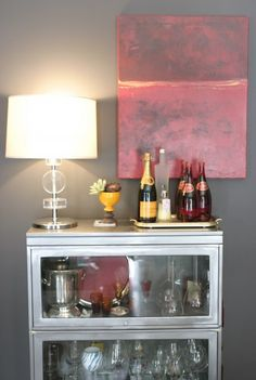 Decorate: Hang art off center and layer objects in front of it for an easy and casual vignette