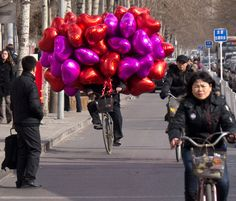 A cyclist with Valentine's Day balloons in Beijing. Look out ahead!!!