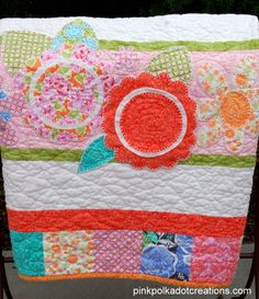 Pink Polka Dot Creations:  Baby quilt.   Fun baby quilt using a charm squares pack!  Easy to put together and so fun with the appliqued flowers and leaves.