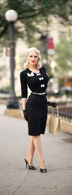 Pale-skinned platinum blonde redly smiling in vintage LBD w/ white belt, sternum bows, & bosom butterfly, black stilettos & gloves carrying cream tote