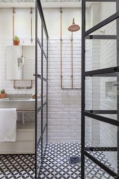 Banheiro tem piso de ladrilho hidráulico, tubulação de cobre aparente e bancada de concreto.