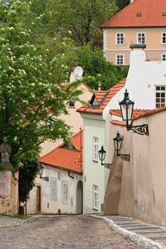 A cobblestone street winds through Hradcany in Prague, Czech Republic